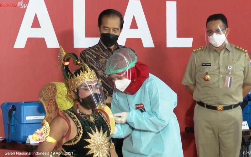 Presiden Joko Widodo (Jokowi) menyaksikan secara langsung proses vaksinasi Covid/19 kepada ratusan seniman dan budayawan di Galeri Nasional Indonesia, Jakarta pada Senin, 19 April 2021 / Youtube Setpres