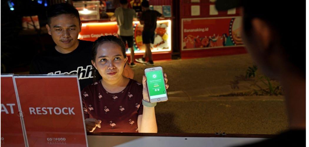 Pengunjung membayar belanja makanan dengan uang digital dari Gojek. - Dimas Ardian / Bloomberg