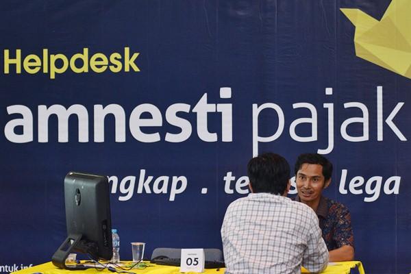 Petugas pajak melayani warga yang mengikuti program Pengampunan Pajak (Tax Amnesty) di Kantor Direktorat Jendral Pajak, Jakarta.