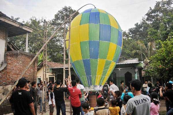 Warga menerbangkan balon udara di Desa Bandung, Kecamatan Diwek, Kabupaten Jombang, Jawa Timur, Minggu (2/7). Tradisi menerbangkan balon udara raksasa bersamaan di tiap musholah ini untuk merayakan Lebaran Ketupat atau biasa disebut Kupatan. - Antara/Syaiful Arif