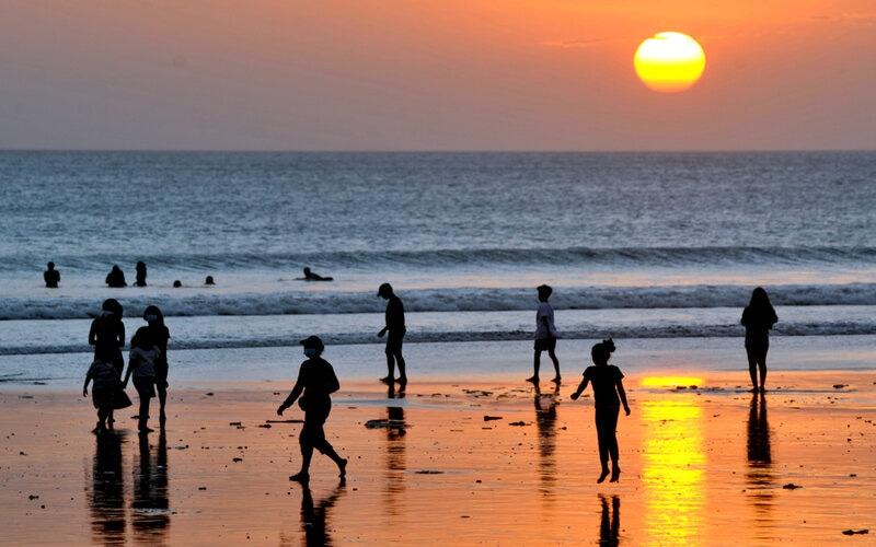 Wisatawan menikmati suasana senja di Pantai Kuta, Badung, Bali, Jumat (14/5/2021). Salah satu destinasi wisata utama di Pulau Dewata tersebut dipadati oleh ribuan wisatawan lokal selama masa liburan Hari Raya Idul Fitri 1442 Hijriah. - Antara/Fikri Yusuf.