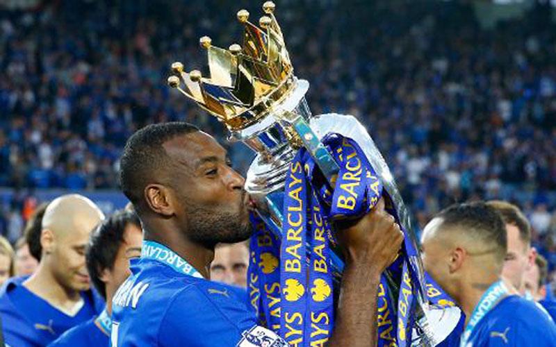 Wes Morgan mencium trofi Liga Primer Inggris setelah Leicester City juara musim 2015-2016. - PremierLeague.com