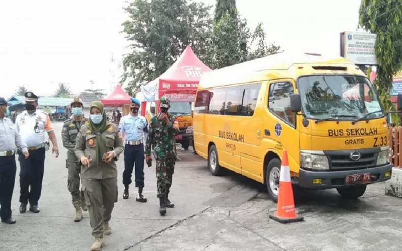 Petugas gabungan melintas di sekitar bus sekolah yang digunakan untuk mengangkut pemudik positif Covid-19 berdasarkan hasil tes usap antigen di Terminal Kalideres, Jakarta Barat, Selasa (18/5/2021). - Antara