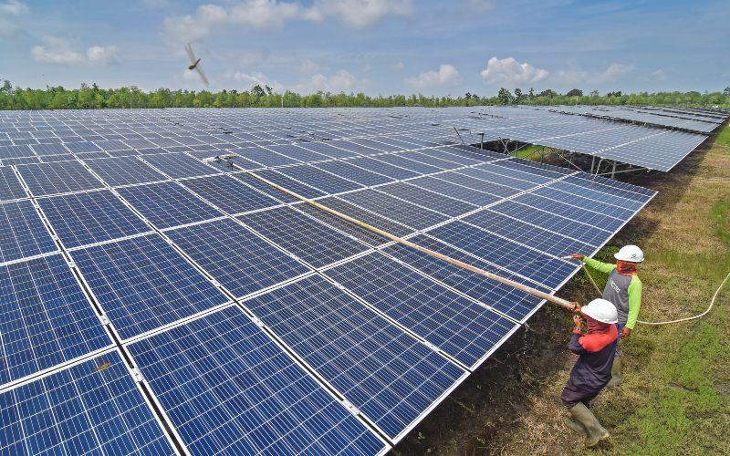 Pekerja membersihkan panel pembangkit listrik tenaga surya (PLTS) di Desa Sengkol, Kecamatan Pujut, Praya, Lombok Tengah, Nusa Tenggara Barat, Selasa (2/2/2021)./Antara - Ahmad Subaidi