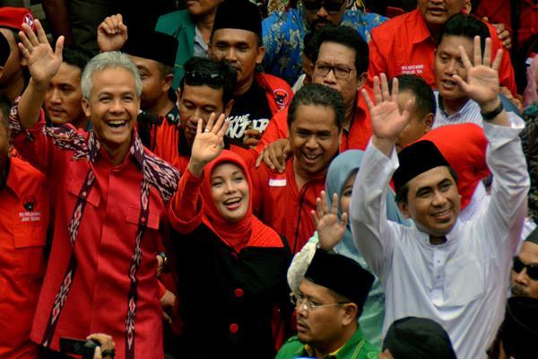 Bakal cagub-cawagub Jawa Tengah Ganjar Pranowo (kiri) dan Taj Yasin (kanan) melambaikan tangan saat tiba di Kantor KPU Jateng untuk mendaftar sebagai cagub-cawagub, di Semarang, Jawa Tengah, Selasa (9/1). Ganjar Pranowo dan Taj Yasin diusung partai PDI Perjuangan, PPP, Nasdem dan Demokrat. ANTARA FOTO - R. Rekotomo