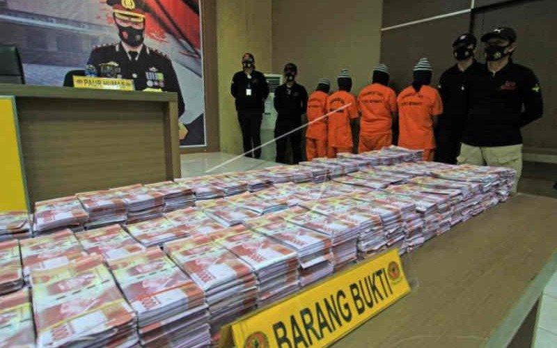Petugas polisi mengamankan barang bukti uang palsu dan tersangka di Mapolres Indramayu, Minggu (23/5/2021) - Antara/Dedhez Anggara