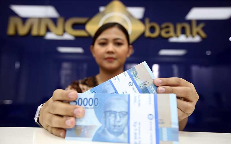 Karyawan menghitung mata uang rupiah di salah satu cabang MNC Bank, Jakarta. Bisnis - Abdullah Azzam