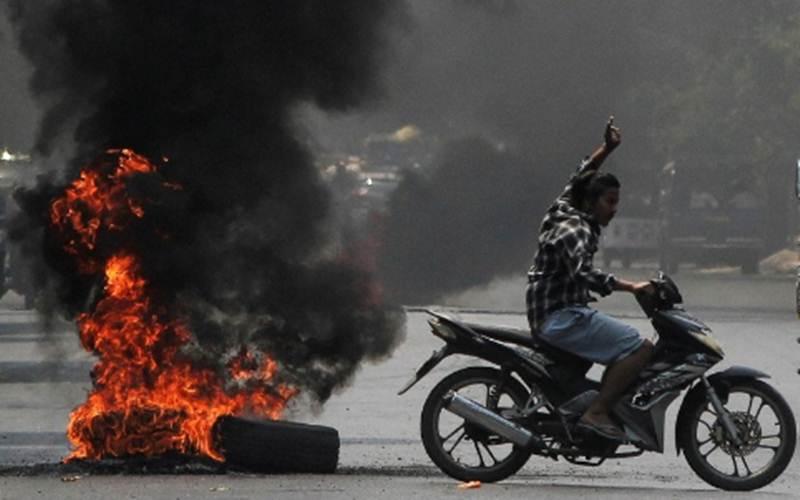 Seorang pria mengacungkan salam tiga jari, simbol perlawanan sipil terhadap kudeta dan junta militer Myanmar, ketika melewati ban terbakar sewaktu unjuk rasa menentang kudeta di Mandalay, Myanmar, 1 April 2021./Antara - Reuters/Stringer