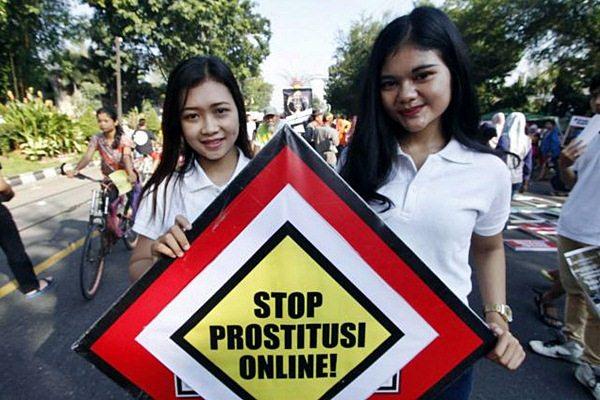 Perwakilan Paguyuban Putra-Putri Solo, Siska Kusumaningrum (kiri), bersama Herlina Tri W membawa poster bertuliskan Stop Prostitusi Online, di Solo, Minggu (10/5). - JIBI/Ivanovich Aldino