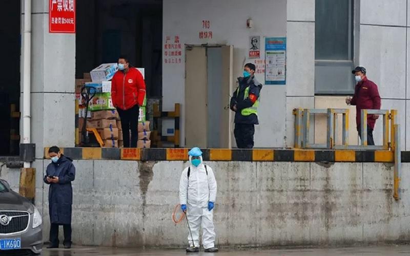 Seorang pekerja menggunakan APD lengkap berdiri di pasar Baishazhou saat kunjungan tim Organisasi Kesehatan Dunia (WHO) yang bertugas menyelidiki asal-usul pandemiCovid-19) di Wuhan, Provinsi Hubei, China (31/1/2021). - Antara/Reuters