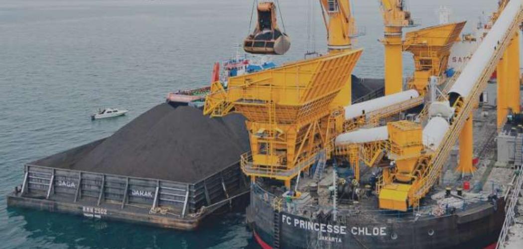 Aktivitas pemindahan muatan batu bara dari tongkang ke kapal induk dengan floating crane oleh anak usaha PT Indika Energy Tbk. (INDY). - indikaenergy.co.id\\r\\n