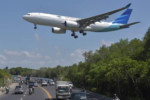Sebuah pesawat udara Garuda Indonesia terbang melintas di atas jalan raya saat bersiap mendarat di Bandara Internasional I Gusti Ngurah Rai, Denpasar, Bali, Senin (14/1/2019).  - Antara/Nyoman Hendra Wibowo