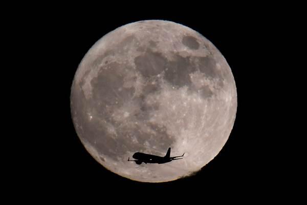 Maskapai penerbangan Inggris British Airways terbang di depan gerhana bulan total di atas langit London, Inggris Raya, 30 Janauri 2018. - Reuters