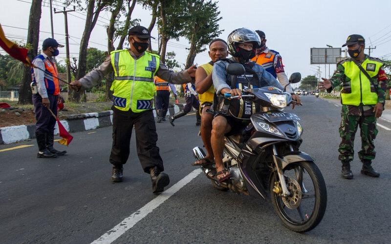 Petugas gabungan menghalau pengendara sepeda motor saat penyekatan arus balik mudik di Desa Balonggandu, Jatisari, Karawang, Jawa Barat, Minggu (16/5/2021). - Antara/M Ibnu Chazar.