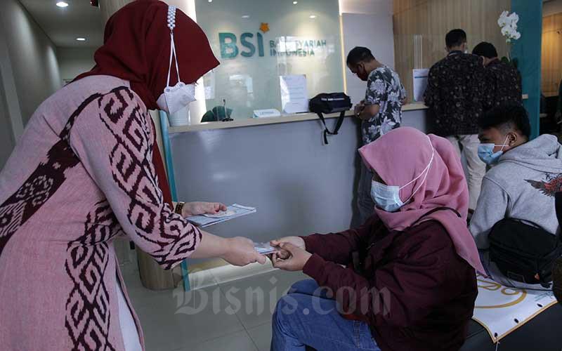 Karyawan melanyani nasabahyang melakukan transaksi di PT Bank Syariah Indonesia KC Jakarta Barat, Kebon Jeruk, Jakarta, Senin (1/2 - 2021). Bisnis