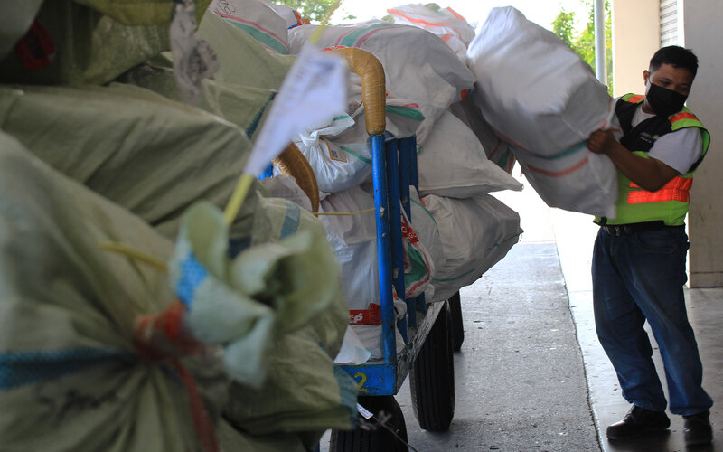 Pekerja mengangkut barang-barang yang baru masuk ke Kargo Bandara Internasional Minangkabau, Selasa (25/5/2021). - Bisnis/Noli Hendra
