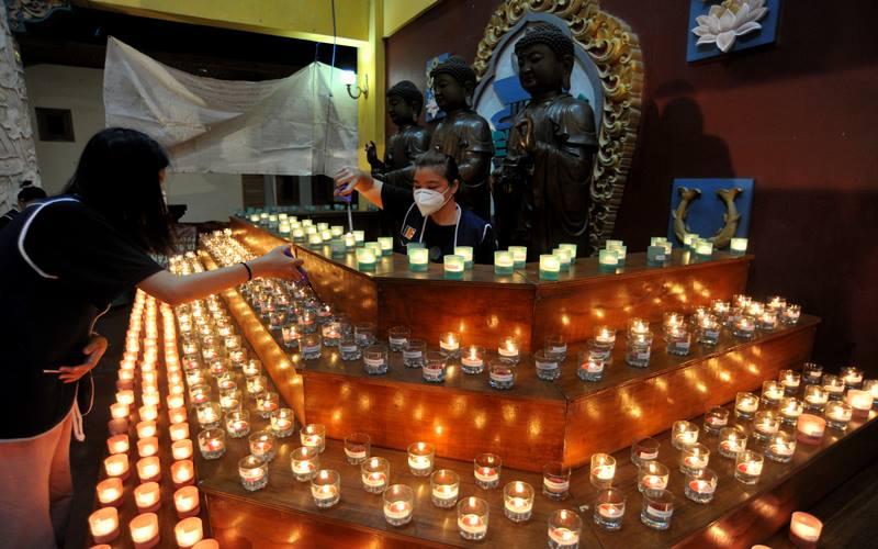 Umat Buddha menyalakan api pelita Waisak, di Vihara Buddha Dharma, Kuta, Bali, Selasa (25/5/2021). Penyalaan ratusan pelita tersebut dilakukan untuk menyambut peringatan Hari Tri Suci Waisak 2565 BE/2021. - Antara