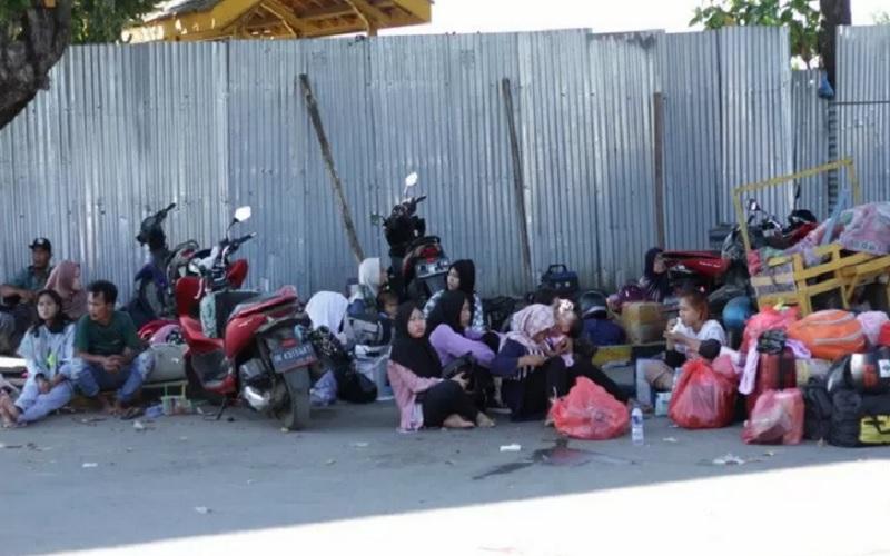 Calon penumpang kapal feri tertahan dan duduk di depan pintu dermaga Pelabuhan Jangkar Situbondo. Senin (3/5/2021). - Antara
