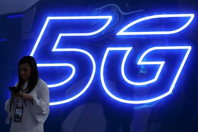 Seorang wanita mengoperasikan ponselnya di dekat logo teknologi 5G. - REUTERS/Sergio Perez