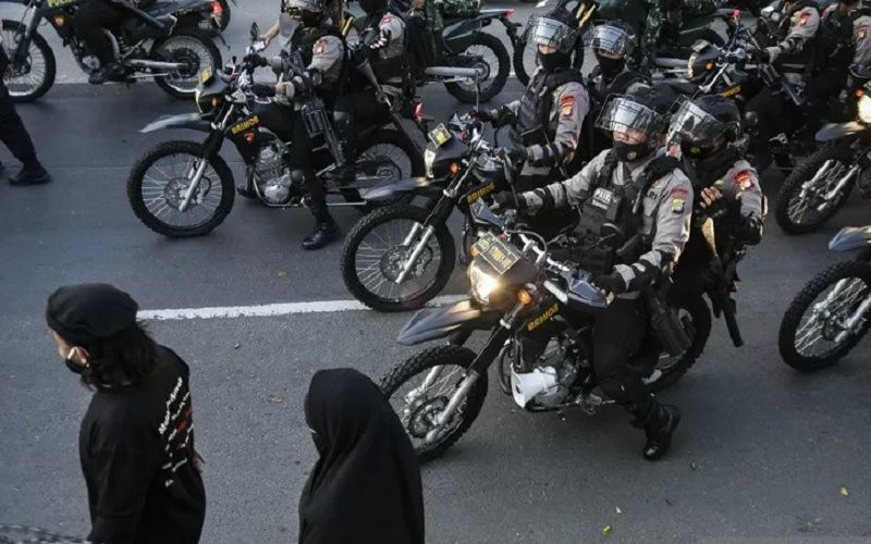 Ilustrasi - Petugas Kepolisian saat membubarkan massa pendukung Muhammad Rizieq Shihab usai sidang di Jalan Raya Penggilingan, Jakarta Timur, Kamis (27/5/2021) terkait kasus kerumunan di Megamendung, Bogor dan Petamburan. - Antara