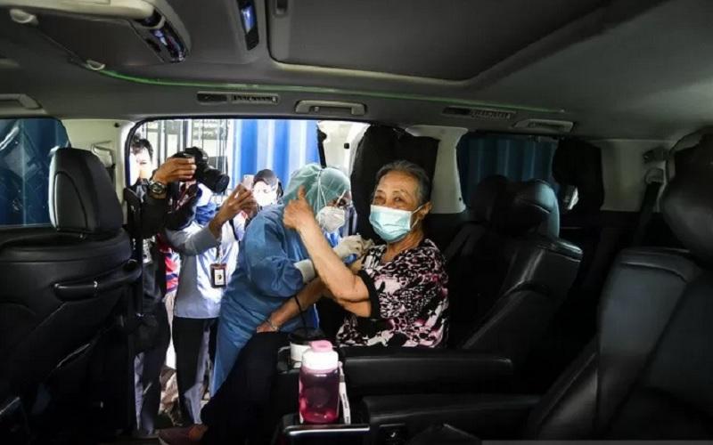 Petugas kesehatan menyuntikan vaksin Covid-19 Sinovac secara drive thru untuk lansia di kawasan Kemayoran, Jakarta, Rabu (3/3/2021). Kementerian Kesehatan menggandeng aplikasi kesehatan halodoc untuk menyediakan layanan vaksinasi Covid-19 untuk lansia secara drive thru, dengan lokasi pertama Pos Pelayanan Program Vaksinasi Covid-19 berada di Bandar Kemayoran Jl. Benyamin Suep Blok C3, Kemayoran, Jakarta Pusat. - Antara