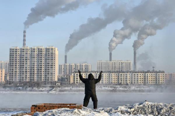 Polusi China: Seorang pria melakukan olahraga pagi dengan latar belakang asap pabrik di seberang sungai Songhua di Provinsi Jilin, China (24/2/2013). - Reuters/Stringer