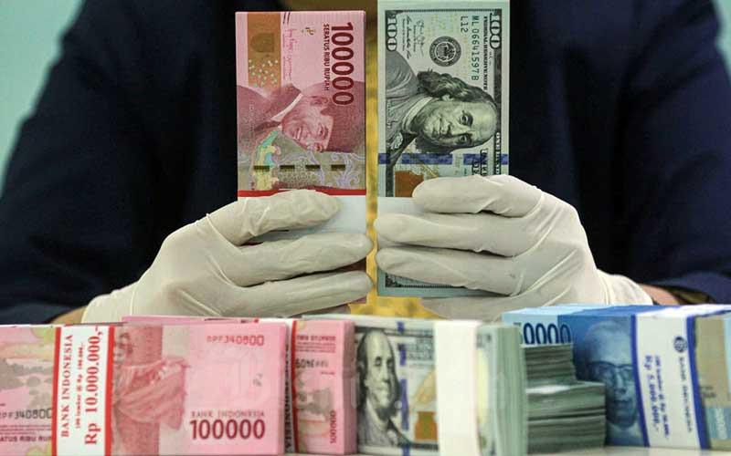 Karyawati salah satu bank memperlihatkan uang rupiah dan dolar di Jakarta, Kamis (29/4/2021). Bisnis - Arief Hermawan P