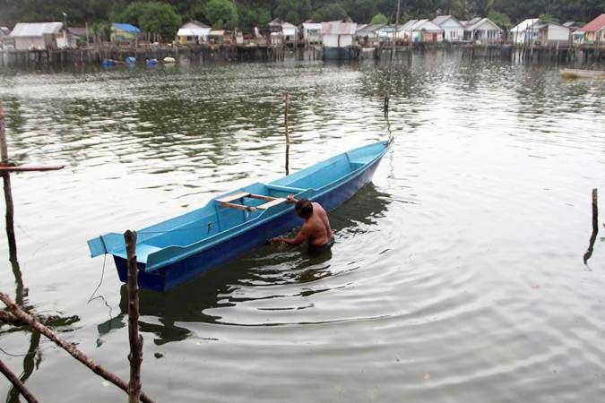 Nelayan membersihkan kapal 3 GT bantuan dari Kementerian Kelautan dan Perikanan di Kelurahan Lapulu, Kendari, Sulawesi Tenggara, Senin (4/2/2019). - ANTARA/Jojon