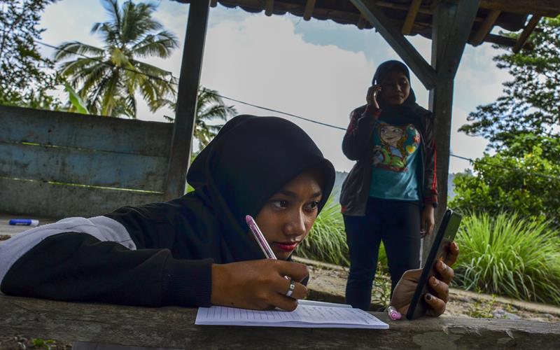 Siswa kelas IX Sekolah Menengah Pertama (SMP) Plus Pasawahan mengerjakan tugas sekolah di pos kamling Desa Pasawahan, Kabupaten Ciamis, Jawa Barat, Kamis, (16/7/2020). Pelajar yang tinggal di desa terpecil terpaksa mengerjakan tugas sekolah di luar rumah lantaran keterbatasan jaringan internet sedangkan sekolah hanya bisa memfasilitasi kegiatan belajar mengajar (KBM) secara daring mengunakan aplikasi WhatsApp Grup serta Facebook Messenger. ANTARA FOTO - Adeng Bustomi