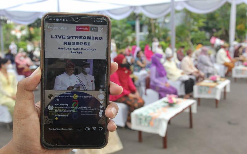 Warga menunjukkan siaran daring Resepsi Hari Jadi ke-728 Kota Surabaya di Balai Kota Surabaya, Jawa Timur, Senin (31/5/2021). Kegiatan resepsi itu digelar dengan menerapkan protokol kesehatan secara ketat sekaligus disiarkan secara daring. - Antara/Didik Suhartono.