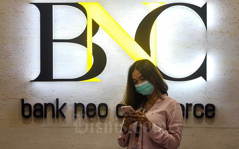 Karyawati beraktivitas di sekitar logo Bank Neo Commerce di Jakarta, Kamis (19/4/2021). Bisnis - Arief Hermawan P