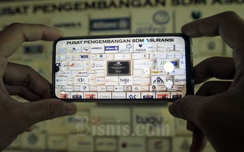 Karyawan memotret deretan logo-logo perusahaan asuransi di Kantor Asosiasi Asuransi Umum Indonesia (AAUI) di Jakarta, Selasa (22/9/2020). Bisnis - Himawan L Nugraha