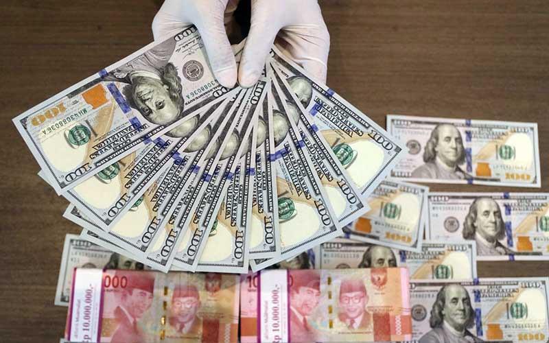 Karyawan menunjukan dolar AS di Jakarta, Rabu (3/3/2021). Bisnis - Eusebio Chrysnamurti