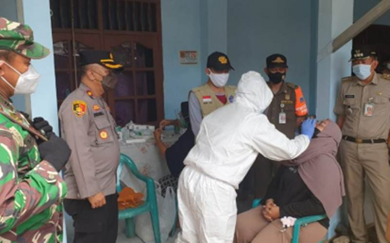 Petugas medis melakukan tes usap antigen kepada warga di RT04/RW02 Srengseng Sawah, Jagakarsa yang menerapkan PPKM skala mikro setelah 14 warganya positif Covid-19, Selasa (25/5/2021)./Antara - HO/Polres Metro Jakarta Selatan