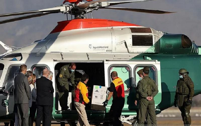 Presiden Chile Sebastian Pinera melihat ke arah pekerja yang membawa kotak vaksin Pfizer-BioNTech Covid-19 ke helikopter, di Bandara Internasional Santiago, Chile, Kamis (31/12/2020). - Antara/Reuters\r\n