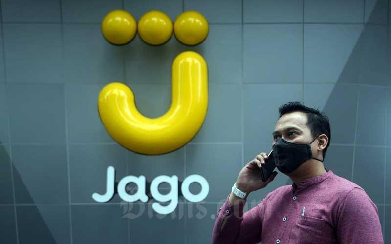 Karyawan beraktivitas di depan logo Bank Jago di Jakarta, Senin (29/3/2021). - Bisnis/Abdurachman