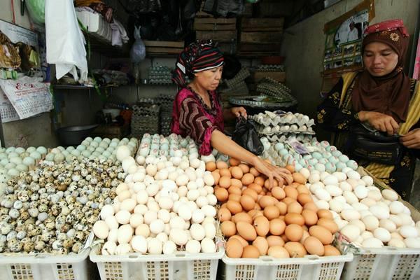 Penjual melayani pembeli telur di pasar Pabean Surabaya, Jawa Timur, Senin (23/5).  - Antara