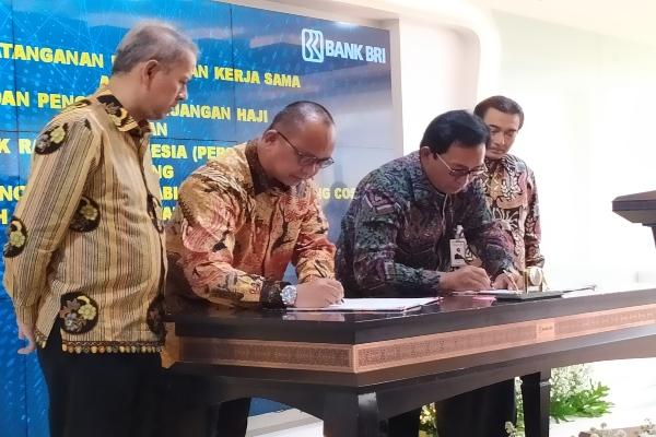 Direktur Hubungan Kelembagaan BRI Sis Apik Wijayanto (kedua kanan) dan Anggota Badan Pelaksana Bidang Keuangan BPKH Acep Riana Jayaprawira (kedua kiri) menandatangani Perjanjian Kerja Sama (PKS) tentang Paket Pekerjaan Penyediaan Bank Notes Saudi Arabian Riyal (SAR) untuk Living Cost Jemaah Haji Reguler Tahun 1440 H / 2019 M di kantor pusat BRI, Jakarta, Senin (24/6/2019). Kegiatan ini disaksikan Direktur Utama Bank BRI Suprajarto dan Kepala Badan Pelaksana BPKH Anggito Abimanyu. - Bisnis/ Muhammad Khadafi
