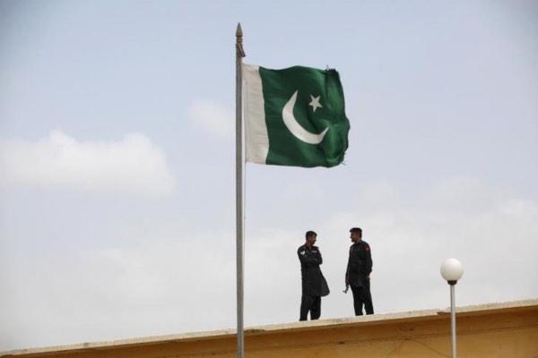 Tentara Pakistan berbincang di dekat bendera Pakistan yang berkibar di penjara Karachi, Pakistan, Jumat (23/8/2013). - Reuters/Akhtar Soomro