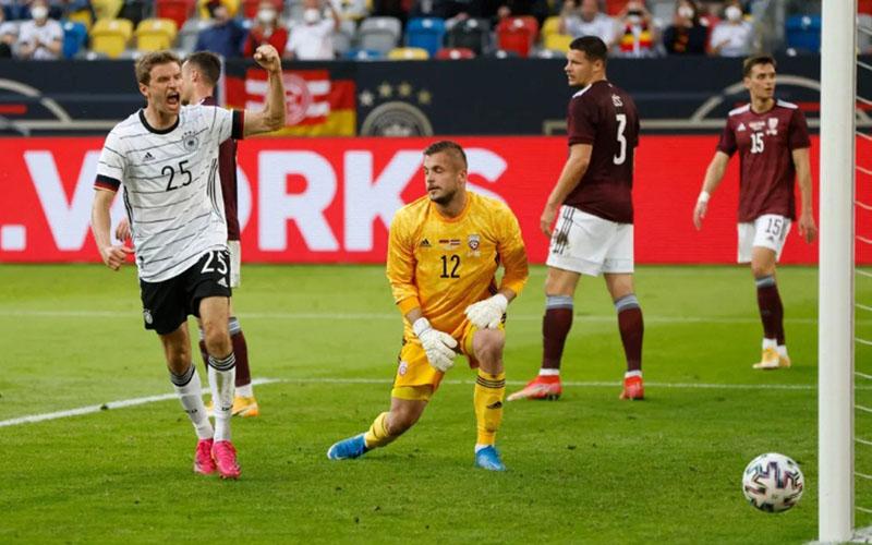 Pemain Jerman Thomas Muller (kiri) menjebol gawang Latvia. - Bundesliga.com