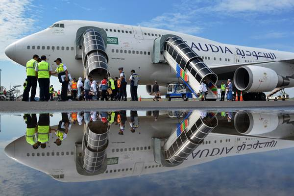 Jemaah calon haji kloter pertama Embarkasi Surabaya berjalan menuju pesawat di Bandara Udara Internasional Juanda, Sidoarjo, Jawa Timur, Jumat (28/7). - ANTARA/Umarul Faruq