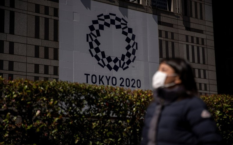 Seorang wanita menggunakan masker berjalan melewati spanduk Olimpiade Tokyo 2020./Antara - Reuters