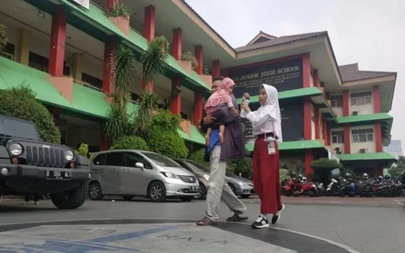 Orangtua siswa mengantarkan anaknya mendaftar sekolah di SMP 115, Jakarta, Senin (24/6/2019). - Antara