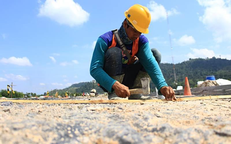 Pekerja beraktivitas di proyek jalan tol Trans Sumatra ruas Padang - Pekanbaru Seksi Padang - Sicincin yang hingga kini progresnya baru mencapai 37,989 persen dari panjang pengerjaan 36,2 kilometer, Sabtu (13/3/2021). - Bisnis/Noli Hendra