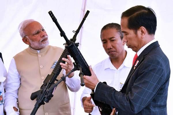 Presiden Joko Widodo (kanan) dan Perdana Menteri India Narendra Modi (kiri) mengamati senjata, di sela-sela pertemuan, di Jakarta, Rabu (30/5/2018). - Setpres