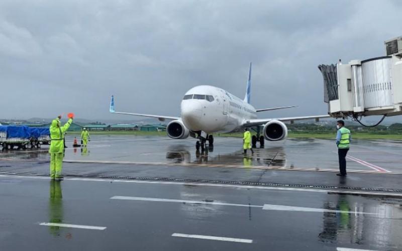 Petugas di Bandara Internasional Ahmad Yani sedang memandu pesawat yang hendak parrkir di tengah hujan lebat. - Istimewa