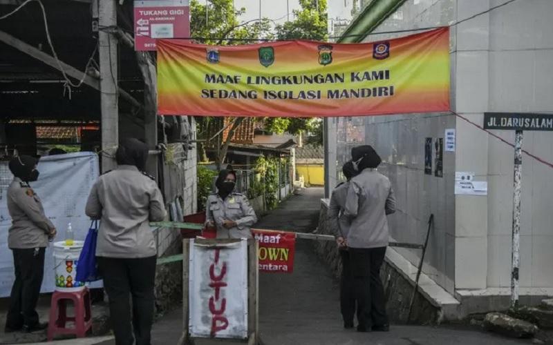 Personel Kepolisian berjaga di kawasan yang sedang menerapkan lockdown skala mikro di Jalan As-Syafiiyah, Cipayung, Jakarta, Jumat (28/5/2021). - Antara\r\n