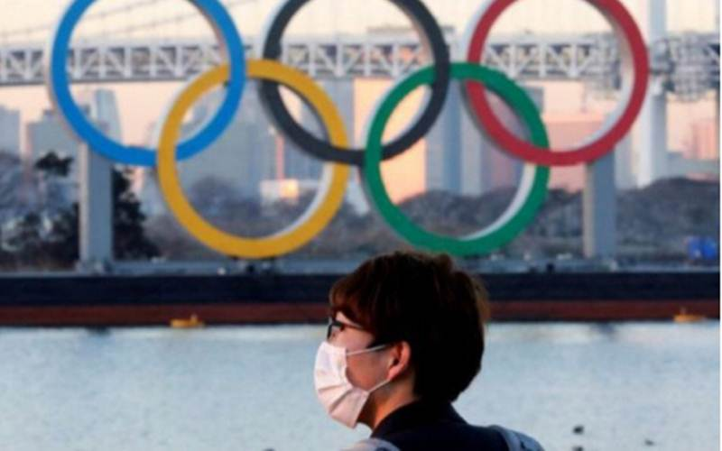 Seorang pria mengenakan masker sedang berdiri di depan logo Olimpiade di Jepang./Antara - Reuters