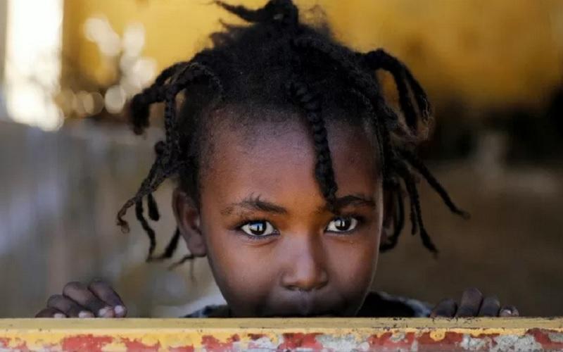 Bocah perempuan berdiri di jendela tempat penampungan sementara, di kamp pengungsian Village 8, menampung pengungsi asal Ethiopia yang menyelamatkan diri dari peperangan di Tigray, dekat perbatasan Sudan-Ethiopia, Sudan, Rabu (2/12/2020). - Antara/Reuters