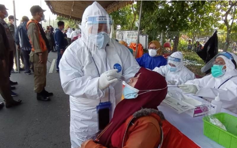 Seorang warga menjalani rapid test antigen di kaki Jembatan Suramadu sisi Kota Surabaya, Selasa (8/6/2021)./Antara - HO/Humas Pemkot Surabaya